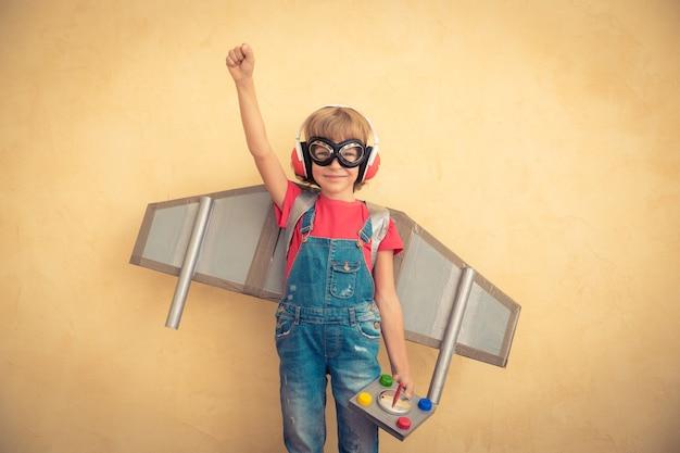 Criança feliz brincando com o jetpack de brinquedo em casa. sucesso e conceito de líder