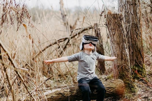 Criança feliz brincando e assistindo a óculos de realidade visual ou tecnologia vr na bela natureza da floresta.