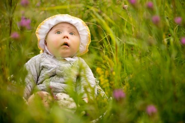 Criança feliz brincando em uma grama. bebê feliz brincando na grama