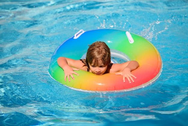 Criança feliz brincando na piscina. férias de verão para crianças.
