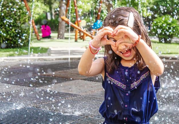 Criança feliz brincando no foco seletivo da fonte.