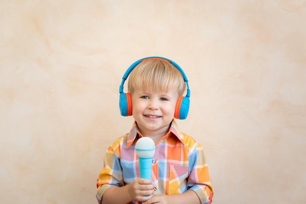Criança feliz cantando uma música. garoto engraçado brincando em casa