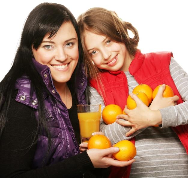 Criança feliz com a mãe segurando laranjas e suco