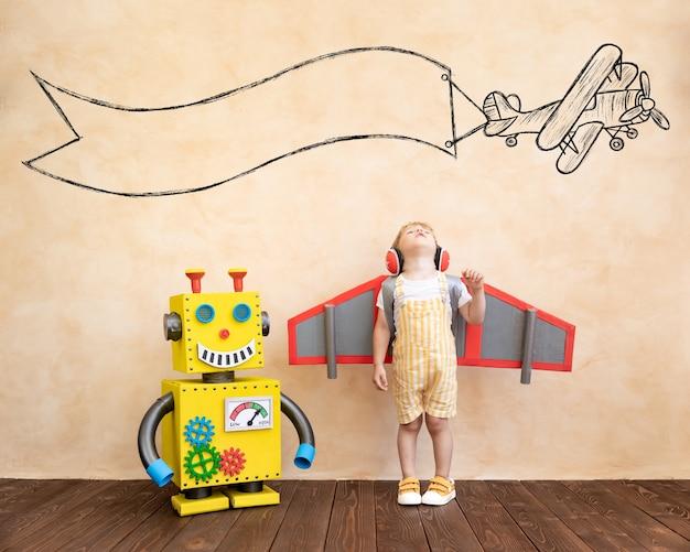 Criança feliz com asas de papelão com robô de brinquedo feito à mão.