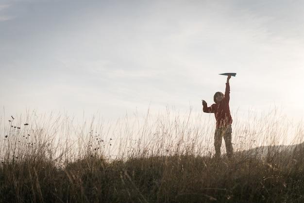 Criança feliz com avião de papel no prado de grama