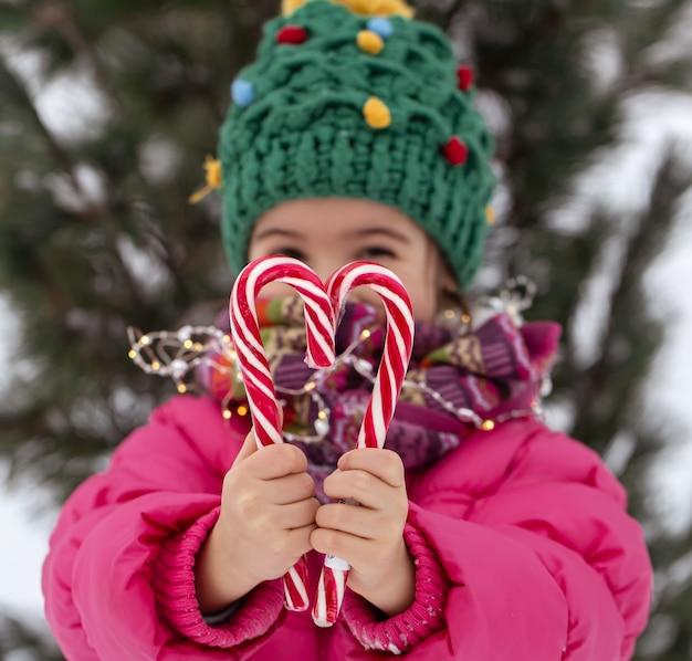 Criança feliz com bastões de doces grandes debaixo de uma árvore de natal. conceito de férias de inverno.