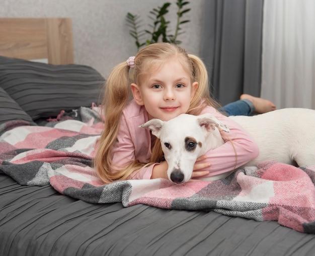 Criança feliz com cachorro. menina do retrato com animal de estimação. jack russell feminino e branco