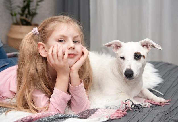 Criança feliz com cachorro. menina do retrato com animal de estimação. menina e branco jack russell