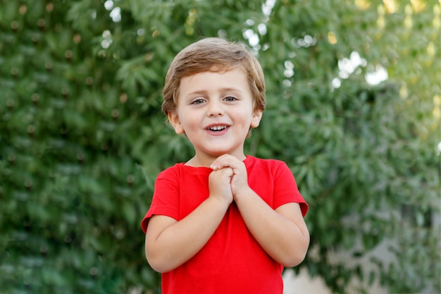 Criança feliz com camiseta vermelha no jardim
