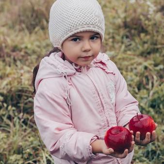 Criança feliz com maçãs vermelhas nas mãos. colheita criança engraçada ao ar livre no parque outono.