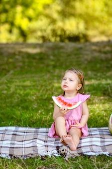Criança feliz com melancia na natureza