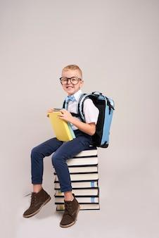 Criança feliz com mochila e pilha de livros