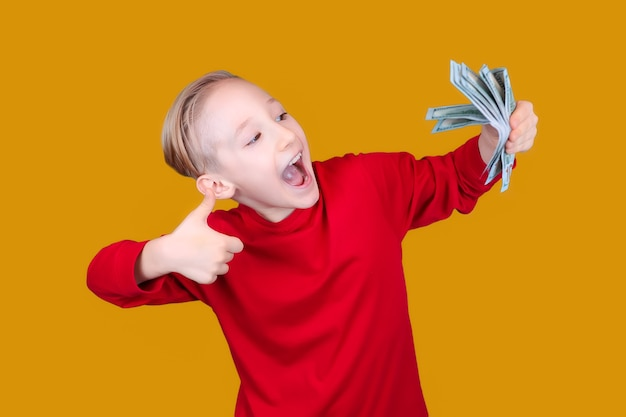 Criança feliz com notas de dinheiro na mão e fazendo sinal de positivo com o polegar