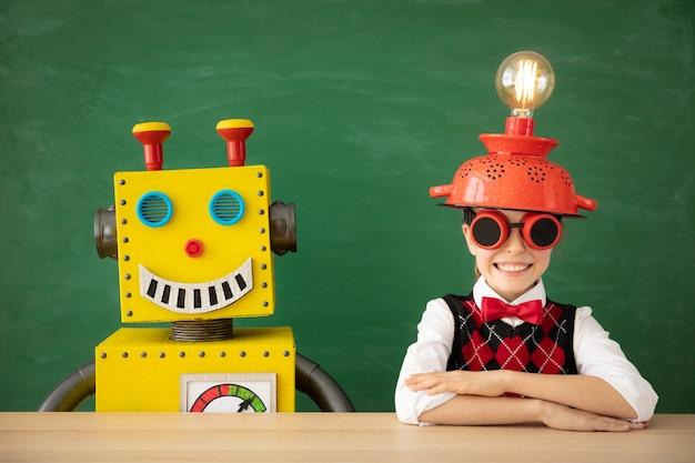 Criança feliz com o robô de brinquedo na escola contra o quadro-negro.