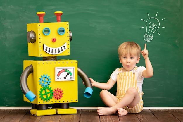 Criança feliz com o robô de brinquedo na sala de aula pré-escolar.