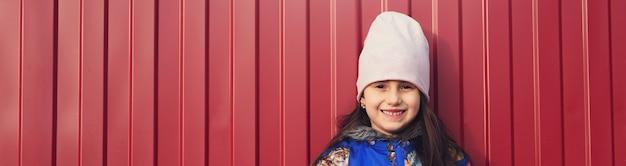 Criança feliz com o smartphone nas mãos em uma superfície vermelha no meio da rua. vestida com uma jaqueta azul e sorrindo.