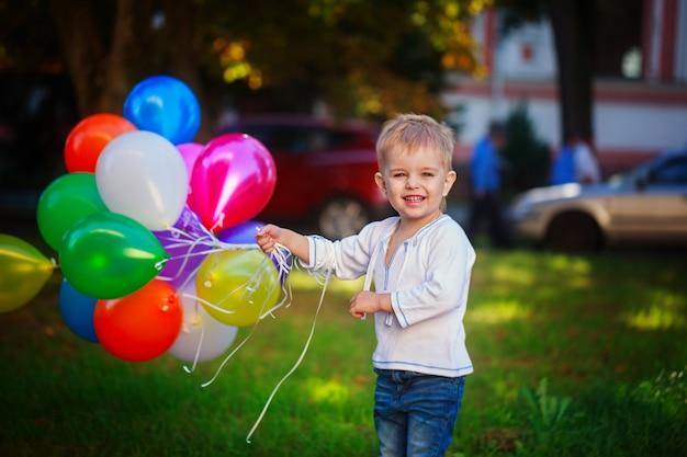 Criança feliz com os balões coloridos do brinquedo ao ar livre. garoto sorridente se divertindo no dia ensolarado de verão