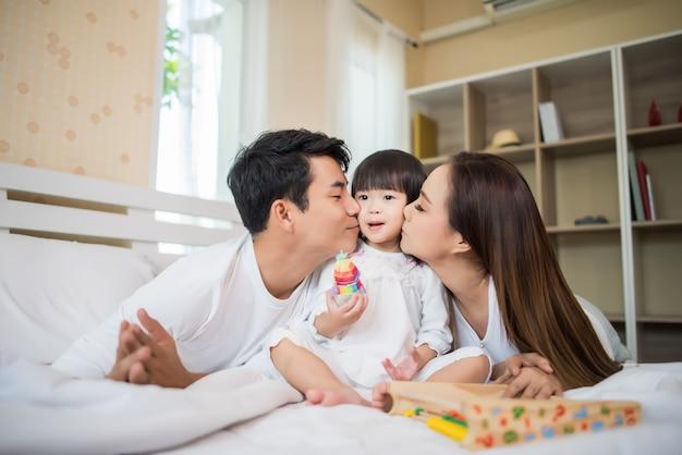 Criança feliz com os pais brincando na cama em casa