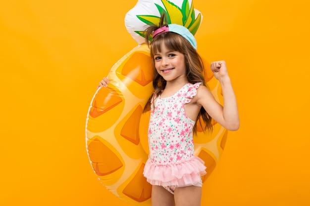 Criança feliz com um boné de beisebol em um maiô com um abacaxi de círculo de natação em uma parede laranja