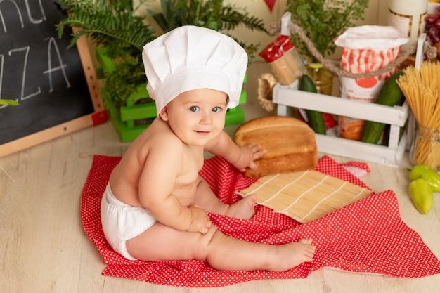 Criança feliz com um chapéu de chef sentada na cozinha com pão