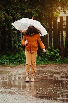 Criança feliz com um guarda-chuva e botas de borracha saltar na poça em uma caminhada