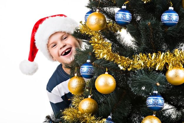 Criança feliz com um presente perto da árvore de natal