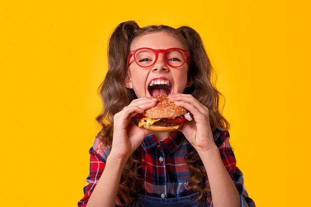 Criança feliz comendo hambúrguer fast food