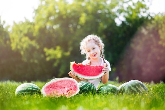 Criança feliz comendo melancia. garoto come frutas ao ar livre. menina brincando no jardim, mordendo uma fatia de melancia.