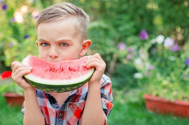 Criança feliz comendo melancia no jardim. as crianças comem frutas ao ar livre. lanche saudável para crianças. menino brincando no jardim, mordendo uma fatia de melancia.