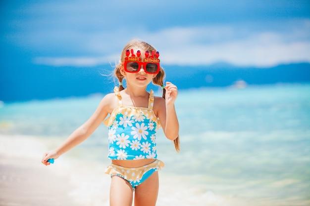 Criança feliz curtindo férias na praia tropical e pronta para nadar