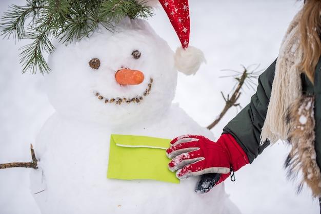 Criança feliz dando uma carta para um boneco de neve em uma caminhada de inverno com neve