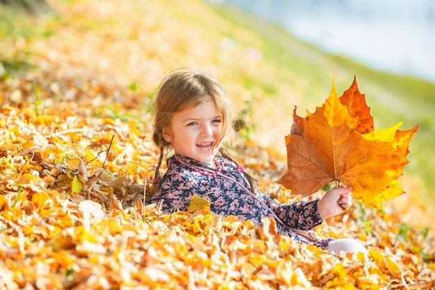 Criança feliz de outono se divertindo com folhas ao ar livre no parque. fundo natural de folhas caindo.