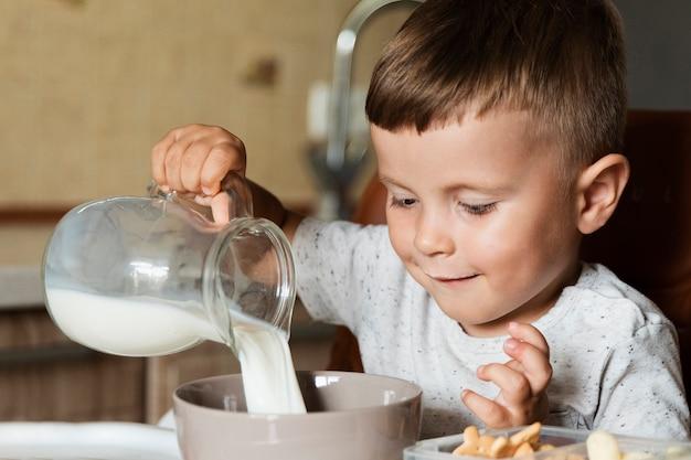 Criança feliz, derramando leite em uma tigela
