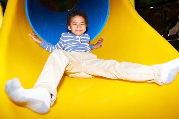 Criança feliz, descendo a corrediça