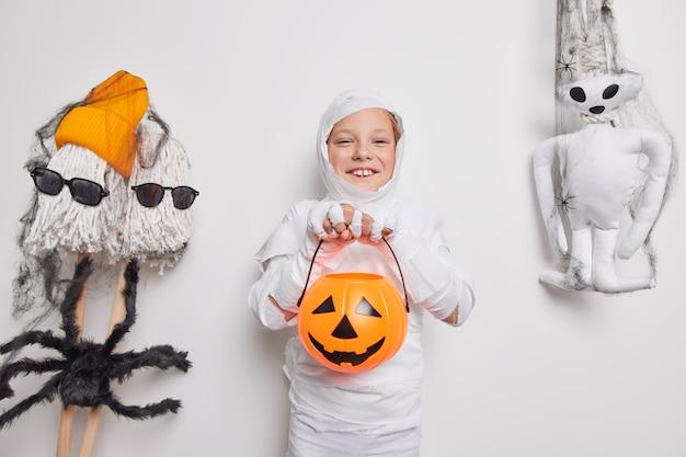 Criança feliz do dia das bruxas brinca de doce ou travessura jack o lantern abóbora embrulhada em tecido branco rodeada por atributos de férias isolados no branco