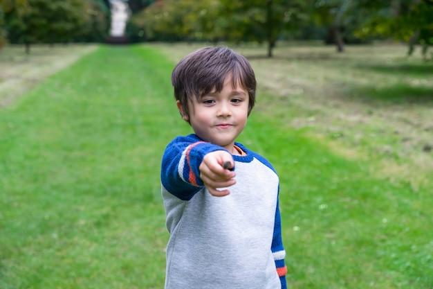 Criança feliz do retrato brincando sozinho no jardim.