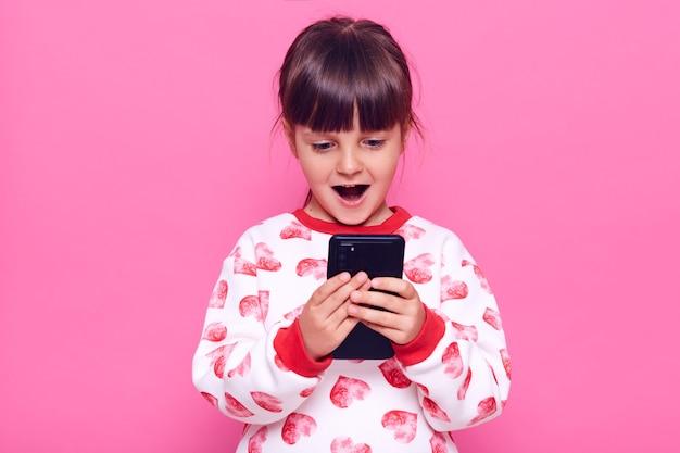 Criança feliz do sexo feminino animado vestindo jumper com corações segurando o telefone celular nas mãos e vê algo surpreendente em sua tela, mantém a boca aberta, posando isolado sobre a parede rosa.