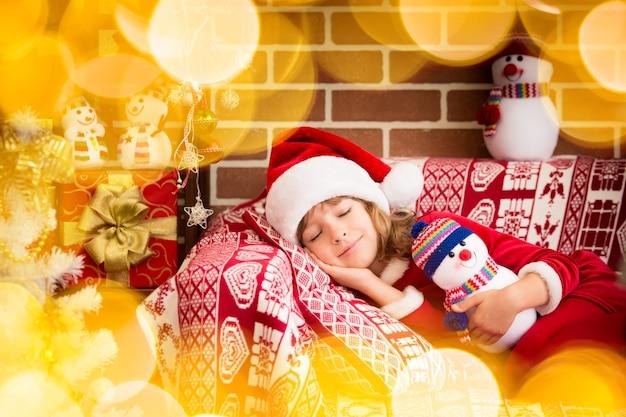 Criança feliz dormindo em casa. criança engraçada usando chapéu de papai noel