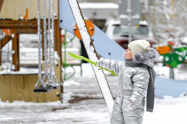 Criança feliz durante o dia em uma caminhada de inverno. uma menina alegre em um macacão prateado quente no playground. o bebê está segurando uma pá de brinquedo. primeira nevasca. fundo desfocado.