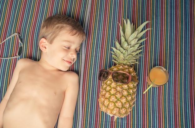 Criança feliz e abacaxi tomando sol sobre uma toalha