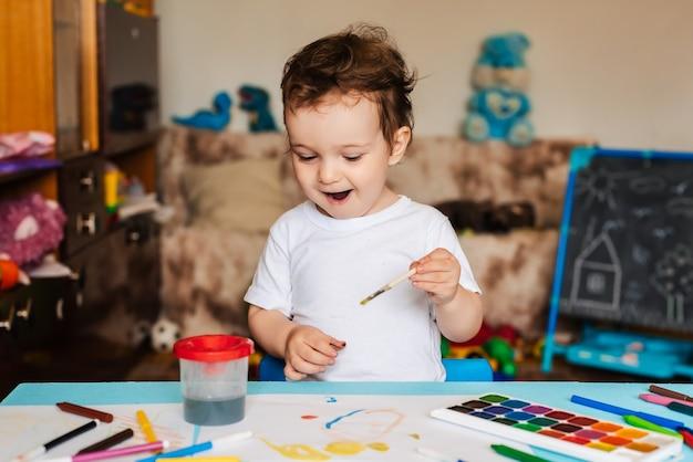 Criança feliz e alegre desenha com um pincel em papel usando tintas multicoloridas