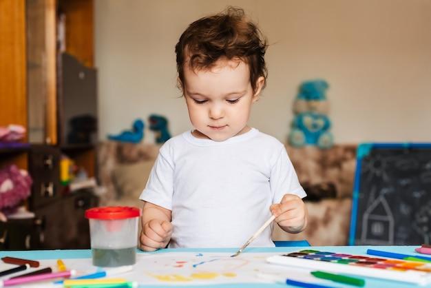 Criança feliz e alegre desenha com um pincel em um álbum usando tintas multicoloridas