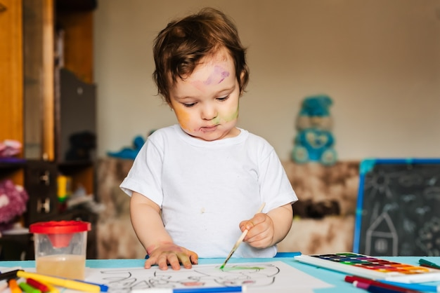 Criança feliz e alegre desenhando com pincel no álbum usando muitas ferramentas de pintura.