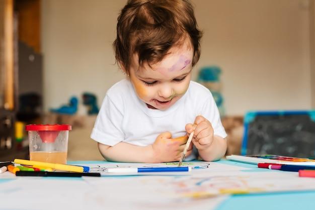 Criança feliz e alegre desenhando com pincel no álbum usando várias ferramentas de pintura.