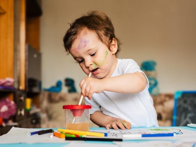 Criança feliz e alegre desenhando com pincel no álbum usando várias ferramentas de pintura
