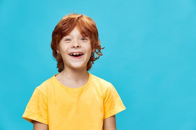 Criança feliz e cheia de energia sorrindo sobre um fundo isolado e uma camiseta amarela cortada