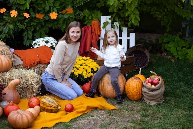 Criança feliz e mãe com abóbora ao ar livre no dia das bruxas