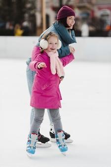 Criança feliz e mãe patinar no gelo