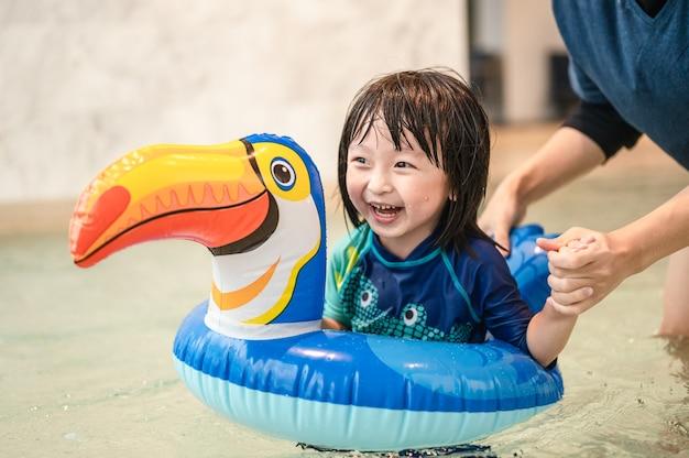 Criança feliz e pai com piscina e anel inflável em forma de calau se divertindo em uma piscina