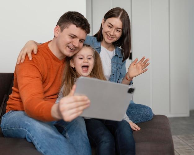 Criança feliz e pais com tablet